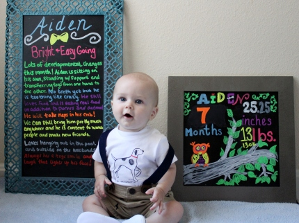 Aiden with seven month milestone chalkboards