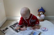 Aiden playing with the sports page of the newspaper