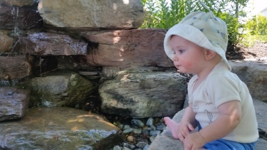 Aiden sitting by a fountain
